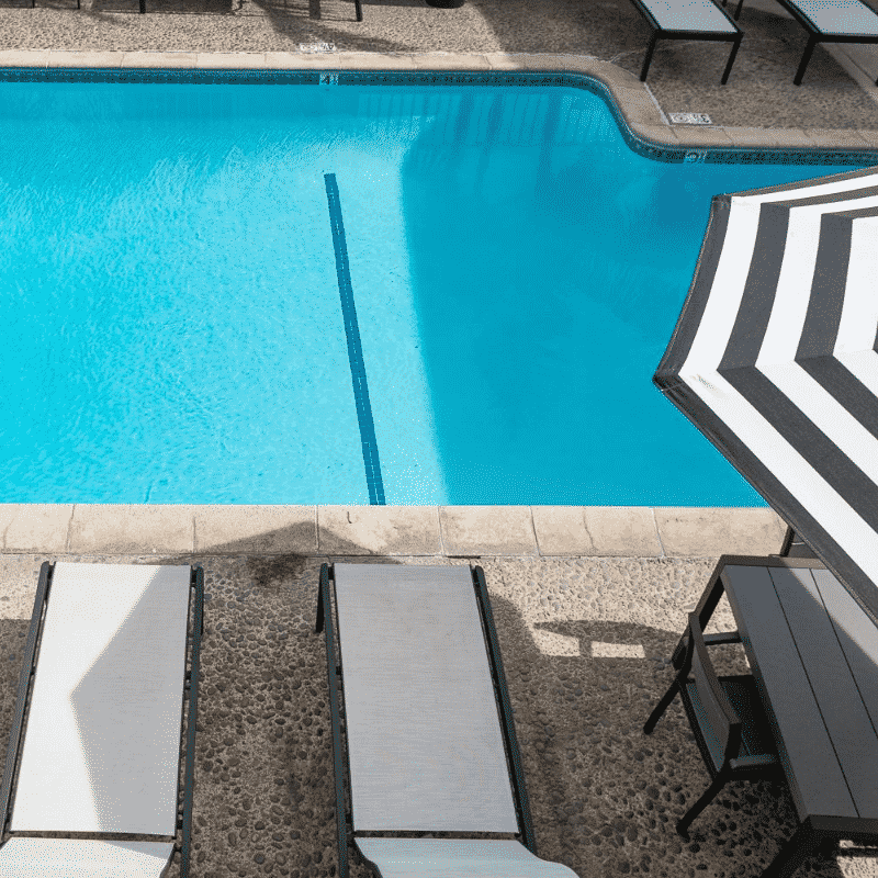 Two pool chairs next to the pool